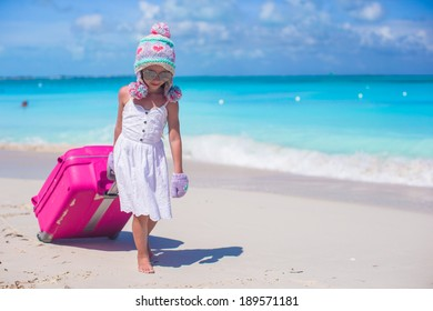 Adorable girl in warm winter hat and mittens walking with luggage on beach