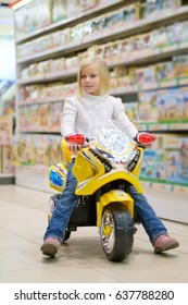 Adorable girl in white sweater ride on toy tricycle in kids store