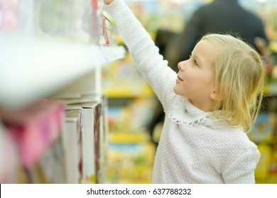 Adorable girl in white sweater select toys dolls on shelves in kids store