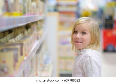 Adorable girl in white sweater select toys on shelves in kids store