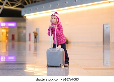Adorable girl in winter outfit inside of airport building with roller suitcase posing