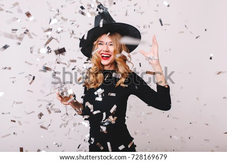 Adorable girl in witch hat having fun with sparkle confetti in her  birthday. Indoor portrait a6a7a5f3ee6c