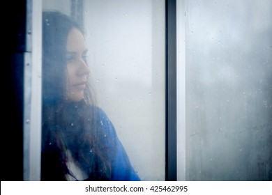 Adorable girl (woman) staying near the window and looking on raindrops, indoors. A girl looks out the window. Vintage color. Unfocusing and foged window. Blue color.