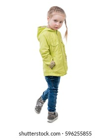 Adorable girl in yellow coat, standing turned, hands in pockets, isolated on white background