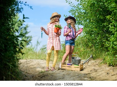Adorable girls in hats going planting plants. Kids siblings having fun at farm. Taking care of plants. Girls with gardening tools. Sisters helping at farm. Eco farming concept. On way to family farm.