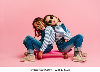 Adorable girls sitting together on a skateboard. Girls in stylish outfit with skateboard on pink background.