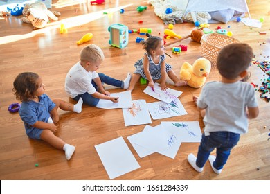 Adorable group of toddlers sitting on the floor drawing using paper and pencil around lots of toys at kindergarten
