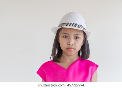 Adorable happy asian kids in a pink dress with white hat.