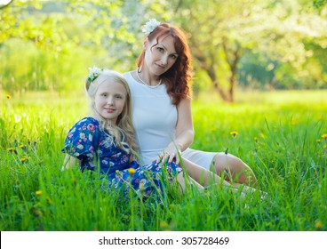 Adorable happy baby girl with mother in a beautiful blooming fruit garden with white blossoms on apple trees.