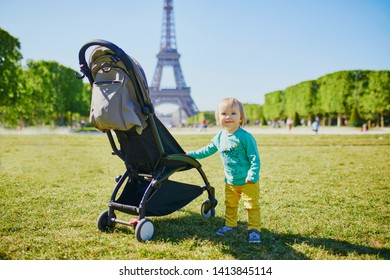 Adorable happy baby girl standing next to her pushchair in Paris near the Eiffel tower. Smiling toddler on vacation in France. Travelling with kids