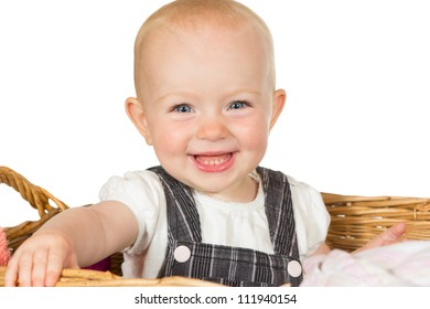 Adorable happy beaming baby with a wide toothy smile sitting in a wicker basket isolated on white