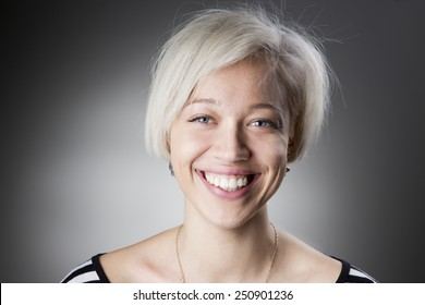 Adorable happy blonde with short hair looking into the camera and smiling a big smile with healthy teeth