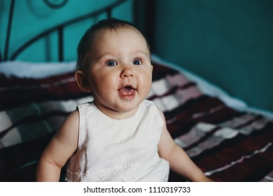 Adorable happy cheerful or surprised toddler girl sitting at home bed. People, emotions, joy, childhood concept