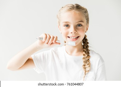 adorable happy child brushing teeth and smiling at camera isolated on white