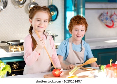adorable happy children in aprons smiling at camera while cooking together in kitchen
