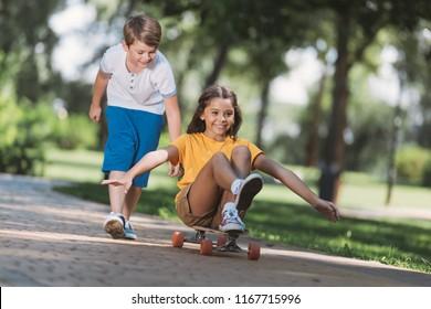 adorable happy children having fun with longboard in park