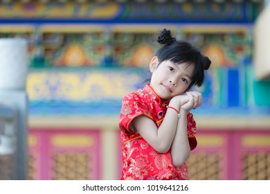 Adorable happy Chinese girl dreaming about envelope gift from her parent for Chinese New Year bless