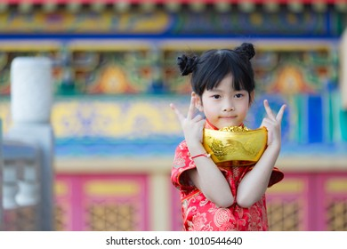 Adorable happy Chinese girl receiving gold bar on Chinese New Year
