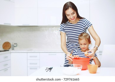 Adorable happy family makes cakes together on your white kitchen.