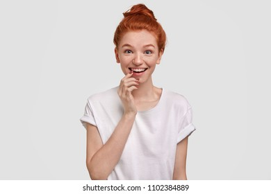 Adorable happy freckled female keeps hand near mouth, dressed in casual white t shirt, poses against studio background. Joyful pretty teenager has foxy hair knot, stands indoor. Emotions concept