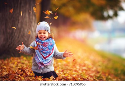 adorable happy girl playing with fallen leaves in autumn park