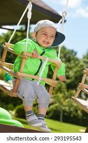 Adorable happy kid swinging outdoors