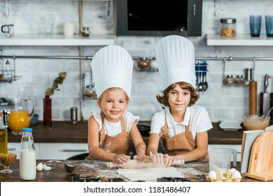 adorable happy kids in chef hats preparing dough for cookies and smiling at camera