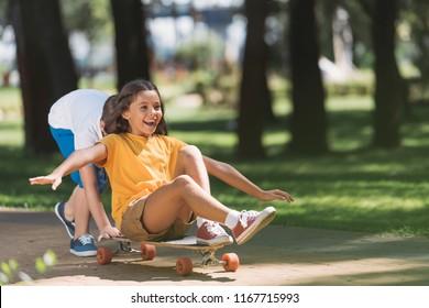 adorable happy kids having fun with longboard in park