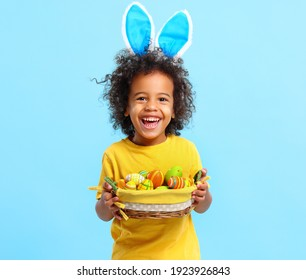 Adorable happy little African American boy with curly hair in casual clothes and bunny ears on head laughing while holding Easter basket