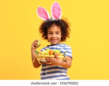 Adorable happy little African American boy with curly hair in striped t shirt  and bunny ears on head laughing while holding Easter basket - Shutterstock ID 1926790202