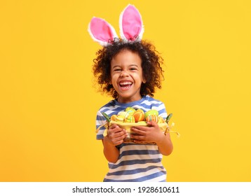 Adorable happy little African American boy with curly hair in striped t shirt  and bunny ears on head laughing while holding Easter basket