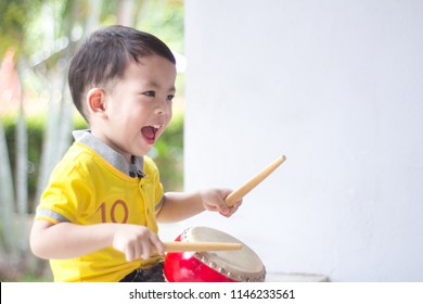 The Adorable happy Little asian boy playing an hit the drum at home.Happy kids.Child development concept.