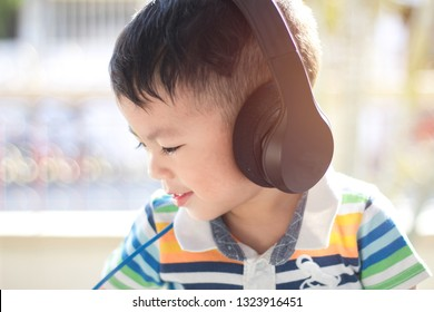 The Adorable happy Little asian boy Listening to the music with  the headphone at the park in the morning. Happy kids.Child development concept.