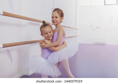 Adorable happy little ballerinas hugging, smiling to the camera, copy space. Cute little ballerina in tutu and leotard embracing her friend at ballet school
