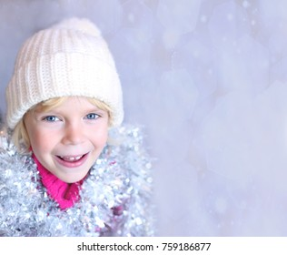 Adorable happy little girl with the Christmas gift. Place for simple text