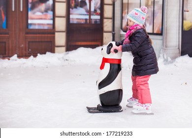 Adorable happy little girl enjoying skating at the ice-rink
