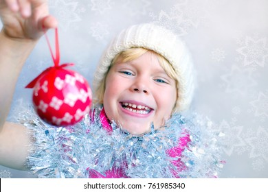 Adorable happy little girl holding Christmas ornament. Space for simple text