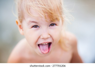 Adorable happy little girl on beach vacation, close up portrait