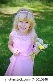 Adorable happy little girl is playing with dandelions