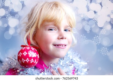 Adorable happy little girl playing with Christmas ornament using it like earring