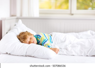 Adorable happy little kid boy after sleeping in his white bed in colorful nightwear near big window with green and yellow autumn foliage. Funny happy child playing and smiling.