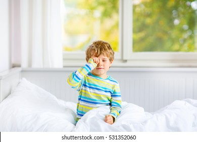 Adorable happy little kid boy after sleeping in his white bed in colorful nightwear near big window with green and yellow autumn foliage. Funny happy child playing and smiling. Family, childhood