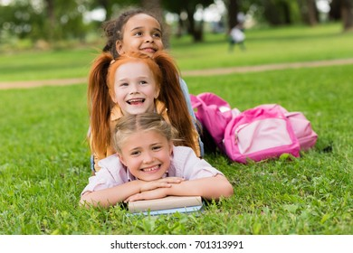 adorable happy multiethnic girls with books lying on grass in park