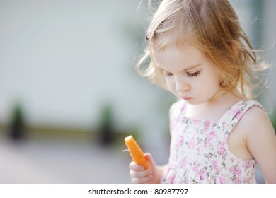 Adorable happy preschooler girl eating carrot outdoors