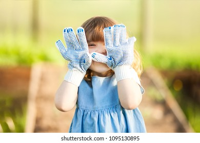 Adorable happy toddler girl in the greenhouse, wearing garden gloves, little gardener, mother's helper