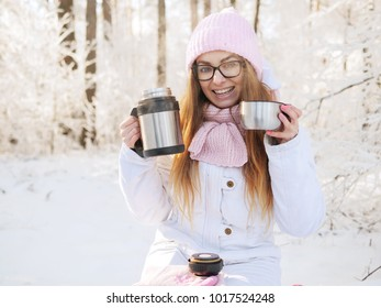 Adorable happy young blonde woman in pink knitted hat scarf having fun drinking hot tea from thermos cup snowy winter park forest in nature