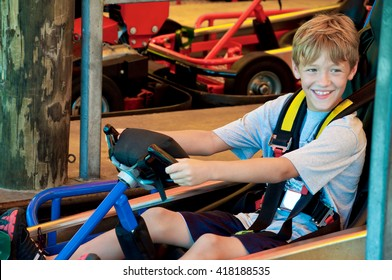 Adorable happy young kid on a go cart at an amusement park looking sideways.