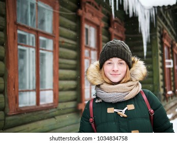 Adorable happy young redhead woman in green parka hat having fun at snowy winter street against green wooden hut