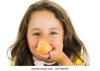 Adorable healthy little girl holding a carrot in front of her face isolated on white