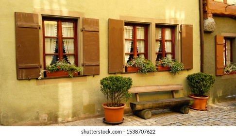 Adorable image of bench and windows from a small italian house